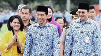 Iriana, Jokowi dan Ahok berjalan bersama saat menghadiri Upacara HUT Korps Pegawai Republik Indonesia (Korpri) ke-43 di halaman Monumen Nasional (Monas), Jakarta, Senin (1/12/2014). (Liputan6.com/Faizal Fanani)