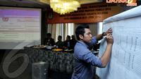 Seorang petugas mencatat hasil penghitungan suara Pileg tingkat kabupaten/kota di Hotel Maharadja, Senin (21/4/14). (Liputan6.com/Johan Tallo)