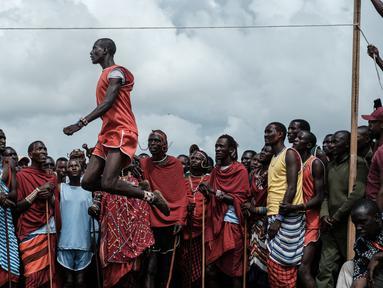Pria suku Masaai melompat untuk mencapai tali selama mengikuti Olimpiade Maasai 2018 di Kimana, Kenya (15/12). Olimpiade ini inisiatif dari kelompok konservasi internasional yang dipimpin oleh Born Free. (AFP Photo/Yasuyoshi Chiba)