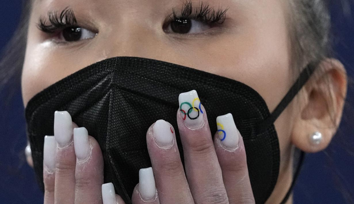 Sunisa Lee, dari Amerika Serikat, menunggu hasil final final all-around senam artistik putri pada Olimpiade Musim Panas 2020 di Tokyo, Jepang, Kamis (29/7/2021). Sunisa Lee memberi hiasan pada kukunya bergambar logo Olimpiade. (AP Photo/Gregory Bull)