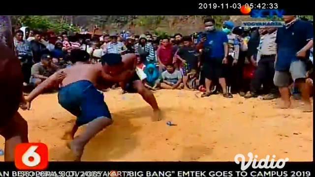 Peserta gulat tradisional Madura (Okol) berusaha saling membanting saat pertandingan, di Desa Akor, Pamekasan, Jawa Timur, Jumat (1/11/2019). Tradisi yang digelar tiap akhir musim kemarau itu sebagai permohonan kepada Tuhan agar turun hujan.