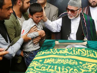 Zabihullah Tamanna, anak seorang wartawan Afghanistan dan sejumlah kerabat saat berdoa di depan peti jenazah Tamanna di sebuah rumah sakit di Kabul, Afghanistan (7 /6/2016). Tamanna tewas setelah diserang pejuang taliban. (REUTERS/Omar Sobhani)
