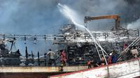 Petugas pemadam kebakaran dibantu pekerja mencoba memadamkan api di kapal nelayan di Pelabuhan Benoa, Denpasar, Bali, Senin (9/7). Hingga saat ini tak ada korban jiwa dalam kebakaran tersebut. (SONNY TUMBELAKA/AFP)