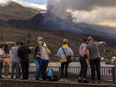 Wisatawan melihat dan berswafoto dengan latar gunung berapi yang meletus di Canary, Pulau La Palma, Spanyol, 26 Oktober 2021. Para pejabat mengatakan gunung berapi yang meletus selama lima minggu terakhir di Pulau La Palma lebih aktif dari sebelumnya. (AP Photo/Emilio Morenatti)