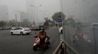 Seorang wanita mengendarai sepeda listrik mengenakan masker di sebuah jalan yang diselimuti kabut asap tebal di Beijing, China (14/11). Pihak berwenang mengeluarkan peringatan kuning untuk polusi udara buruk pada hari Rabu. (AP Photo/Andy Wong)