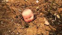Sebuah kepala bayi terlihat berada di atas permukaan tanah dengan menunjukkan senyum menakutkan di wajahnya.