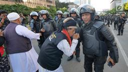Peserta aksi mencium tangan Polisi dari kesatuan Brimob saat gelar doa bersama di depan kantor Bawaslu, Jakarta, Jumat (24/5/2019). Mereka datang untuk mendoakan para demonstran yang meninggal saat aksi 21-22 Mei, pasca hasil penghitungan suara Pemilu 2019. (Liputan6.com/Herman Zakharia)