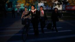 Orang-orang menyeberang jalan saat sore hari di Pyongyang, Korea Utara, (20/10). (AP Photo / Dita Alangkara)
