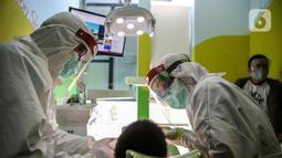 Dokter menggunakan APD memeriksa gigi pasien anak di klinik Medikids kawasan Kemang, Jakarta Selatan, Selasa (7/7/2020). Pelayanan dokter gigi dengan menggunakan APD lengkap  untuk memenuhi protokol kesehatan guna mencegah penyebaran covid-19 di era kenormalan baru. (Liputan6.com/Faizal Fanani)
