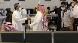 Penumpang saling menyapa saat bersiap terbang dari Bandara Internasional King Abdulaziz, Jeddah, Arab Saudi, Senin (177/5/2021). Warga Saudi yang telah menerima vaksinasi Covid-19 diizinkan bepergian ke luar negeri untuk pertama kalinya sejak Maret 2020. (AP Photo/Amr Nabil)