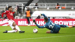 Penyerang Manchester United, Marcus Rashford, berebut bola dengan kiper Newcastle United, Karl Darlow, pada laga Liga Inggris di Stadion St. James' Park, Minggu (18/10/2020). MU menang telak dengan skor 4-1. (Owen Humpreys/PA via AP)