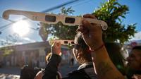 Wisatawan mencoba kaca mata khusus untuk melihat gerhana matahari total di Vicuna, Coquimbo, di gurun Atacama, Santiago, Chile (1/7/2019). Fenomena ini akan menyebabkan bumi gelap gulita dalam sesaat karena cahaya matahari tertutup seluruhnya oleh bayangan bulan. (AFP Photo/Martin Bernetti)