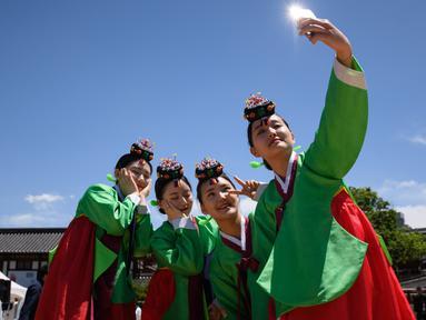 """Para wanita muda berswafoto mengenakan pakaian tradisional hanbok setelah upacara """"Coming of Age"""" di Namsan Hanok Village, Seoul, Senin (20/5/2019). Di Korea Selatan, Coming of Age Day atau hari kedewasaan dirayakan secara nasional setiap tahun pada hari Senin ketiga di bulan Mei. (Ed JONES/AFP)"""