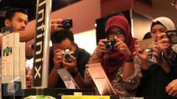 Pengunjung memfoto Smartphone Infinix Zero 3 saat peluncuran perdana di Jakarta, Senin (29/2/2016). Infinix Zero 3 hadir dengan mengusung spesifikasi kelas atas yang menawarkan kualitas kamera diatas rata-rata. (Liputan6.com/Angga Yuniar)