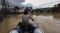 Seorang pria menaiki perahu karet saat menyusuri banjir yang melanda Jalan Bina Warga Rt 005/Rw 07 Kelurahan Rawa Jati, Jakarta, Senin (8/2/2021). Banjir setinggi 60-190 cm tersebut disebabkan oleh luapan air Sungai Ciliwung dan curah hujan Jakarta yang tinggi. (Liputan6.com/Johan Tallo)