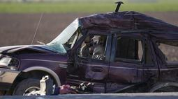 Petugas memilah bukti dan puing-puing di lokasi kecelakaan mematikan truk yang menabrak mobil SUV di Holtville, California (2/3/2021). Sopir truk gandeng itu kini dirawat karena cedera ringan. (AP Photo/Gregory Bull)