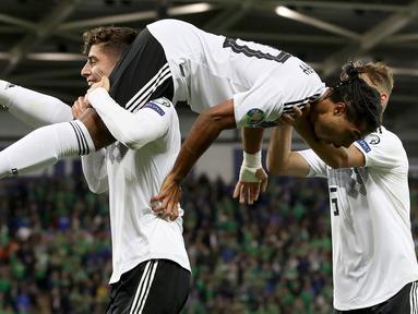 Pemain tengah Jerman, Serge Gnabry (tengah) merayakan golnya ke gawang Irlandia Utara saat bertanding dalam kualifikasi Euro 2020 di Windsor Park, Belfast, Senin (9/9/2019). Jerman berhasil merebut puncak klasemen grup C kualifikasi Euro 2020 usai mengalahkan Irlandia Utara 2-0. (Paul Faith/AFP)