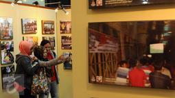 Pengunjung berfoto di antara koleksi foto relawan Jokowi yang dipamerkan di Plaza Atrium Senen, Jakarta, Sabtu (23/4/2016). Hingga 29 April mendatang, Relawan Jokowi menggelar pameran foto dukungan dan diskusi. (Liputan6.com/Helmi Fithriansyah)