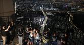 Pengunjung memakai masker untuk melindungi dari penyebaran Covid-19, berselfie saat menginap di lokasi perkemahan semalam di atap gedung pencakar langit di Seoul, Korea Selatan (7/8/2020). Menara Lotte World, setinggi 555 meter gedung pencakar langit dengan 123 lantai. (AP Photo/Lee Jin-man)