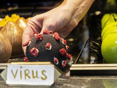 Seorang pramusaji mengambil makanan penutup berbentuk virus corona Covid-19 di sebuah kafe di Praha pada 06 Oktober 2020. Dengan lebih dari 81.000 kasus di Republik Ceko, tingkat penyebaran Covid-19 termasuk yang terburuk di Eropa - hampir separah di Spanyol. (Michal Cizek / AFP)