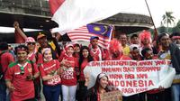 Suporter Malaysia membentangkan bendera terbalik saat berfoto bersama dengan pendukung Indonesia jelang semifinal SEA Games di Stadion Shah Alam, Sabtu (26/8/2017). (Liputan6.com/Cakrayuri Nuralam)