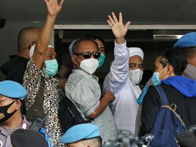 Rizieq Shihab (tengah) melambaikan tangan sesaat sebelum masuk gedung utama Mapolda Metro Jaya, Jakarta, Sabtu (12/12/2020). Rizieq Shihab akan menjalani pemeriksan sebagai tersangka penghasutan dan kerumunan di tengah pandemi Covid-19. (Liputan6.com/Helmi Fithriansyah)