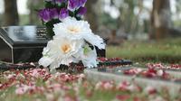 Karangan bunga diletakkan di batu nisan sebuah kuburan di Taman Pemakaman Umum di Jakarta Selatan.  (Liputan6.com/Heppy Wahyudi)