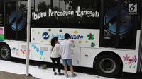 Sejumlah anak berkebutuhan khusus melukis bus Transjakarta di halaman Balai Kota, Jakarta, Jumat (20/4). Kegiatan tersebut dalam rangka memperingati Hari Kartini. Tema lukisan yang diangkat adalah 'Ibuku Perempuan Tangguh'. (Liputan6.com/Arya Manggala)