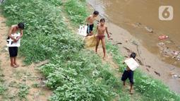 Anak-anak berjalan di pnggir Sungai Ciliwung, Jatinegara, Jakarta Timur, Sabtu (4/7/2020). Minimnya lahan bermain menyebabkan anak-anak tersebut bermain tidak pada tempatnya, meski dapat membahayakan keselamatan. (Liputan6.com/Immanuel Antonius)