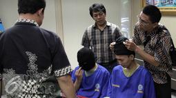 Petugas memakaikan penutup muka ke tersangka  saat rilis penangkapan 6.642 gram narkotika golongan 1 jenis sabu di gedung BNN, Jakarta, Jumat (7/8/2015). Empat tersangka merupakan jaringan Internasional asal Nigeria. (Liputan6.com/Helmi Afandi)