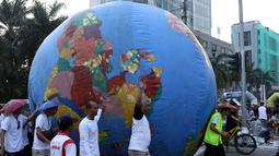 Replika bola dunia berukuran besar digelindingkan di sekitar kawasan Bundaran HI, Jakarta, Minggu (16/9). Acara ini bagian dari peringatan Hari Ozon Sedunia 2018 dengan tema Keep Cool and Carry on! The Montreal Protocol. (Liputan6.com/Helmi Fithriansyah)
