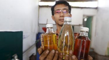 Hamidi memegang tiga botol berisi bahan bakar yang berasal dari pembakaran sampah plastik di bengkel kerjanya dekat TPA Rawa Kucing, Tangerang, (17/3). Hamidi membuat inovatif yang mengubah sampah plastik menjadi bahan bakar. (REUTERS / Beawiharta)