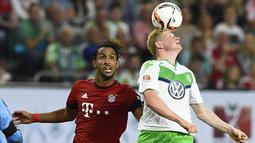 Kevin De Bruyne duel udara dengan Medhi Benatia pada laga German Supercup di Wolfsburg, Sabtu (1/8/205). De Bruyne pindah dari Wolfsburg ke Manchester City dengan nilai transfer 55 juta poundsterling. (AFP Photo/Tobias Schwarz)