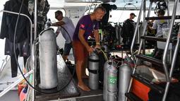 Penyelam memeriksa tangki oksigen saat bersiap melanjutkan pencarian korban kapal wisata yang terbalik di dermaga Chalong, Phuket, Sabtu (7/7). Sebanyak 56 penumpang dilaporkan hilang pada Jumat pagi sebelum upaya penyelamatan dimulai. (AFP/Mohd RASFAN)