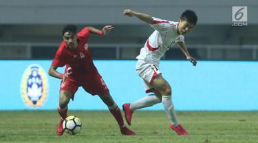 Pemain belakang Bahrain, Husain Sabba (kiri) berebut bola dengan bek Korea Utara, O Chol Hyok pada laga PSSI Anniversary Cup 2018 di Stadion Pakansari, Kab Bogor, Kamis (3/5). Laga dimenangkan Bahrain 4-1. (Liputan6.com/Helmi Fithriansyah)