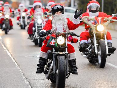Pengendara berpakaian seperti Sinterklas mengendarai sepeda motor selama acara amal di Lustadt, Jerman, Kamis (6/12). Mereka mengumpulkan sumbangan untuk rumah sakit Sterntaler di Speyer, yang merawat anak-anak penderita kanker. (Uwe Anspach/dpa/AFP)