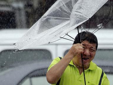 Seorang pria Taiwan memperbaiki payungnya saat melawan angin kencang yang ditimbulkan oleh topan Lekima di Taipei, Taiwan (9/8/2019). Topan Lekima saat ini tengah menghantam Taiwan, membawa angin ribut dengan kecepatan 190 km/jam. (AP Photo / Chiang Ying-ying)
