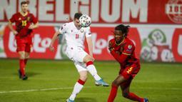 Striker Belarusia, Nikolai Signevich (tengah) melepaskan tendangan saat menghadapi Belgia dalam laga Kualifikasi Piala Dunia 2022 Zona Eropa Grup E di King Power Stadium, Belgia, Selasa (30/3/2021). Belarusia kalah 0-8 dari Belgia. (AP/Francisco Seco)