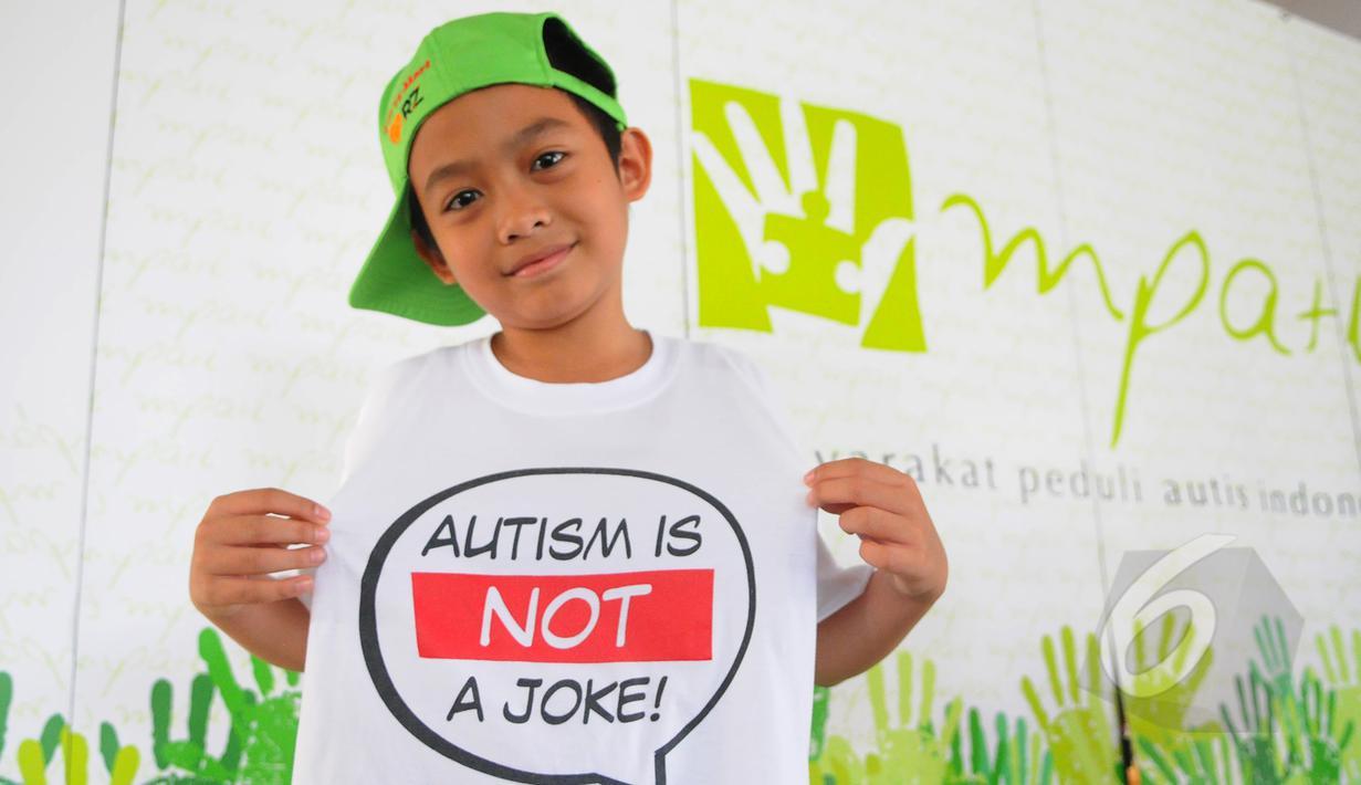 "Seorang anak menunjukkan kaos bertuliskan ""Autism is Not a Joke"" saat acara Fun Walk 2015 di Balaikota DKI Jakarta, Minggu (29/3/2015). (Liputan6.com/Herman Zakharia)"
