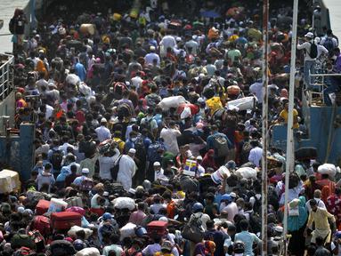 Orang-orang berkerumun saat menaiki kapal feri menuju kampung halaman menjelang perayaan Idul Fitri di tengah pandemi Covid-19 di Munshiganj, Bangladesh pada 9 Mei 2021. Ratusan orang bergegas untuk pulang ke rumah sehingga dapat berkumpul dengan keluarga pada momen Lebaran. (Munir Uz zaman/AFP)