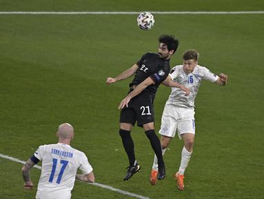 Gelandang Jerman, Ilkay Gundogan (tengah) dan bek Islandia, Alfons Sampsted bersaing memperebutkan bola pertandingan kualifikasi Piala Dunia 2022 Zona Eropa Grup J di Duisburg, Jumat (26/3/2021) dinihari WIB. Ilkay Gundogan mengantar Jerman melumat Islandia 3-0. (Tobias SCHWARZ/AFP/POOL)