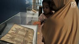Pengunjung melihat salah satu koleksi mushaf Alquran yang dipamerkan di Museum Bayt Al-Quran, Jakarta, Minggu (19/5/2019). Puluhan mushaf Alquran yang berada di Bayt Al-Quran  dikumpulkan sejak abad ke-16. (merdeka.com/Iqbal Nugroho)