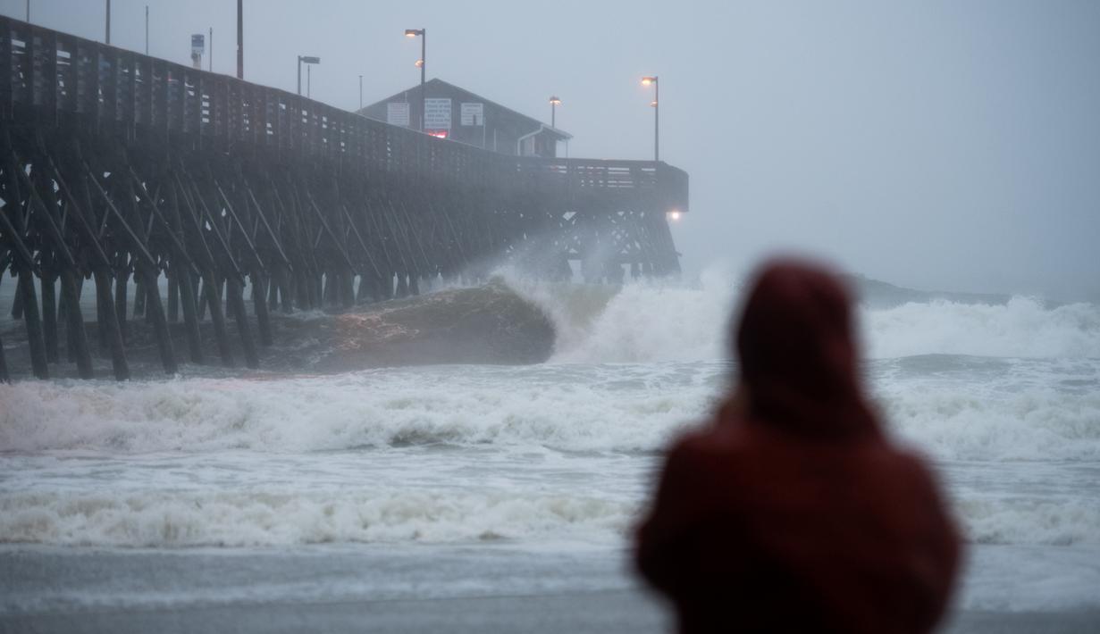Seseorang menyaksikan ombak menabrak Dermaga di Garden City, Carolina Selatan (3/8/2020). Badai Isaias terus bergerak ke utara di sepanjang pesisir timur AS. (Sean Rayford/Getty Images/AFP)