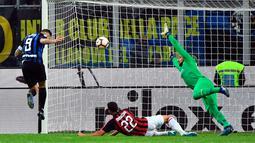 Pemain Inter Milan, Mauro Icardi (kiri) menyundul bola ke gawang AC Milan pada laga Serie A di Stadion San Siro, Milan, Italia, Minggu (21/10). Gol tunggal Icardi membawa Inter Milan menang atas AC Milan. (Daniel Del Zennaro/ANSA via AP)