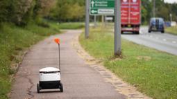 Robot otonom bernama Starship melakukan perjalanan untuk mengantarkan bahan makanan dari supermarket Co-op di Milton Keynes, Inggris, 20 September 2021. Robot Starship bertugas mengantarkan belanja dan makanan. (DANIEL LEAL-OLIVAS/AFP)
