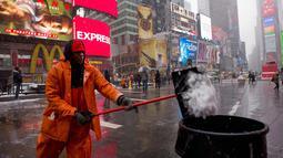 Michael Vante membersihkan salju di New York Times Square, (21/3). Badai salju yang melanda sebagian Amerika Serikat telah membawa salju dan angin kencang. (AP Photo / Mary Altaffer)