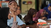 Warga menerima Kartu Lansia Jakarta (KLJ) saat pendistribusian di Jakarta Islamic Center, Koja, Rabu (24/4). Penerima KLJ mendapatkan Rp 600.000 per bulan sebagai bentuk pemberian bantuan sosial untuk pemenuhan kebutuhan dasar bagi lanjut usia. (merdeka.com/Iqbal S. Nugroho)