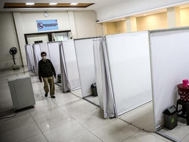 Petugas melintasi ruang isolasi mandiri pasien COVID-19 di Gelanggang Remaja Kecamatan Pademangan, Jakarta, Senin (28/9/2020). Sebanyak 30 bilik isolasi pasien Covid-19 disediakan dengan fasilitas tempat tidur, lemari, dan peralatan mandi. (Liputan6.com/Faizal Fanani)
