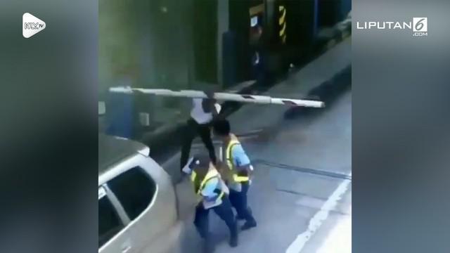 Setelah membantu mendorong mobil yang sedang mogok, pria ini malah mendapat nasib apes setelah tertimpa palang pintu parkir.