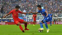 Ahmad Alfarizi coba melewati Asnawi Mangkualam pada uji coba Arema vs Timnas Indonesia U-22 di Stadion Kanjuruhan, Kabupaten Malang, Minggu (10/2/2019). (Bola.com/Iwan Setiawan)
